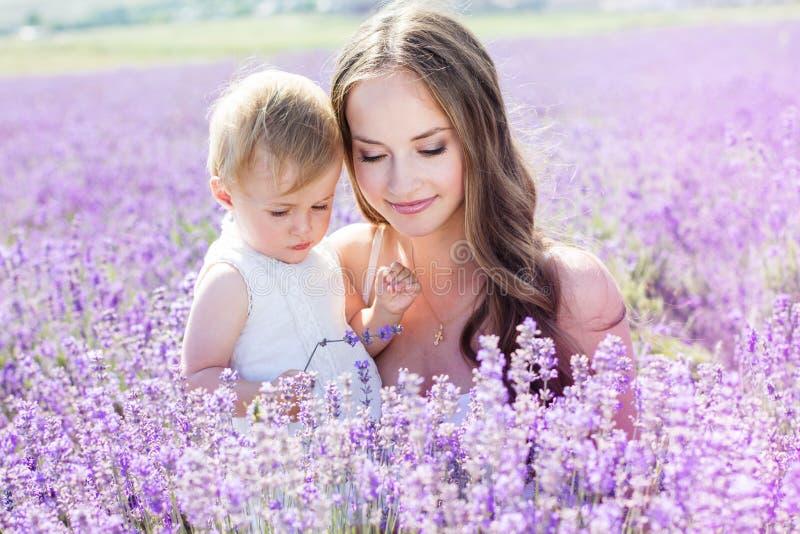 Moder och gaughter som spelar i lavendelfält royaltyfri fotografi