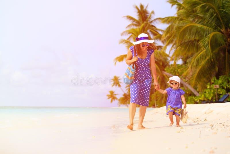 Moder och gullig liten daugther som går på stranden royaltyfria foton