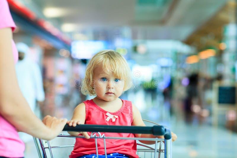 Moder och gullig liten dotter på bagagevagnen in royaltyfria bilder