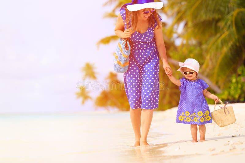 Moder och gullig liten dotter som går på stranden royaltyfri foto