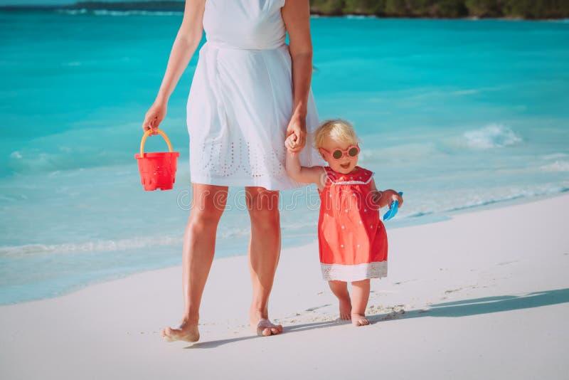 Moder och gullig liten dotter som g?r p? stranden arkivfoto