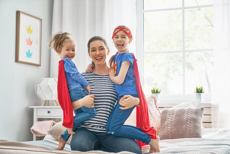 Moder och hennes barn som tillsammans spelar arkivfoto