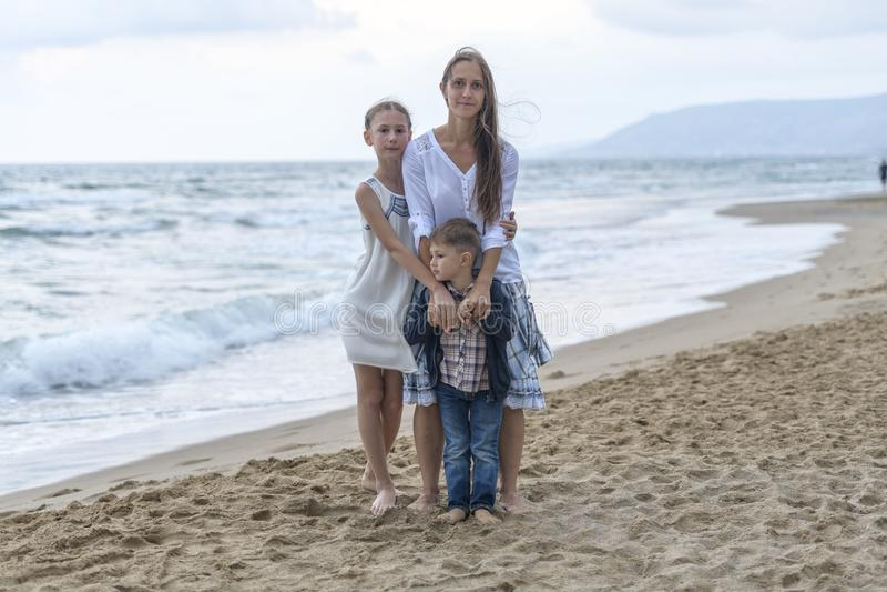 moder och hennes dotter och son på stranden arkivbilder
