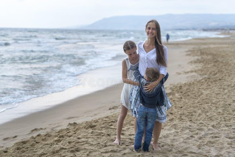 moder och hennes dotter och son på stranden royaltyfria bilder