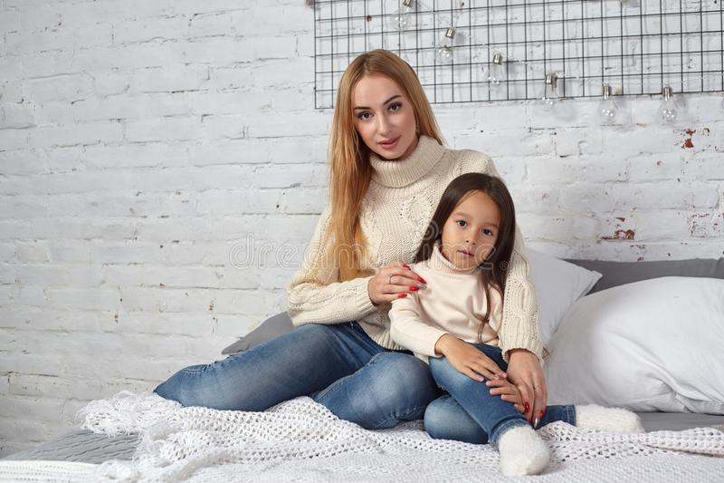Moder och hennes dotterbarnflicka som spelar och kramar på säng arkivbild