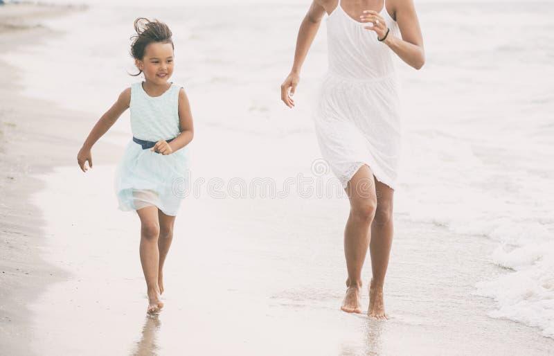 Moder och hennes dotterspring och hagyckel på stranden arkivfoton