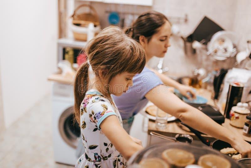 Moder och hennes lilla dotter som lagar mat pannkakor för frukosten i det lilla hemtrevliga köket fotografering för bildbyråer