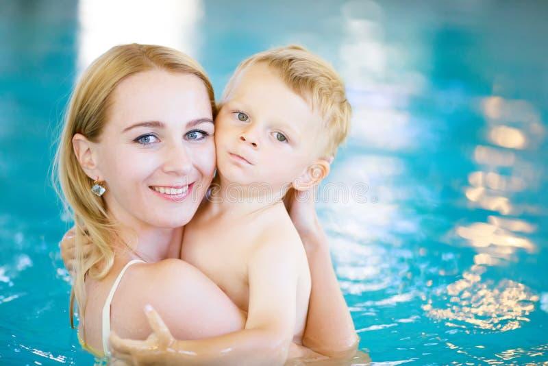 Moder och hennes litet barnsonsimning i pölen royaltyfria bilder