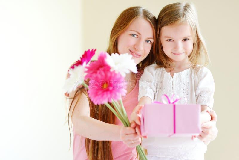 Moder och honom dotter som ger en gåva royaltyfria foton