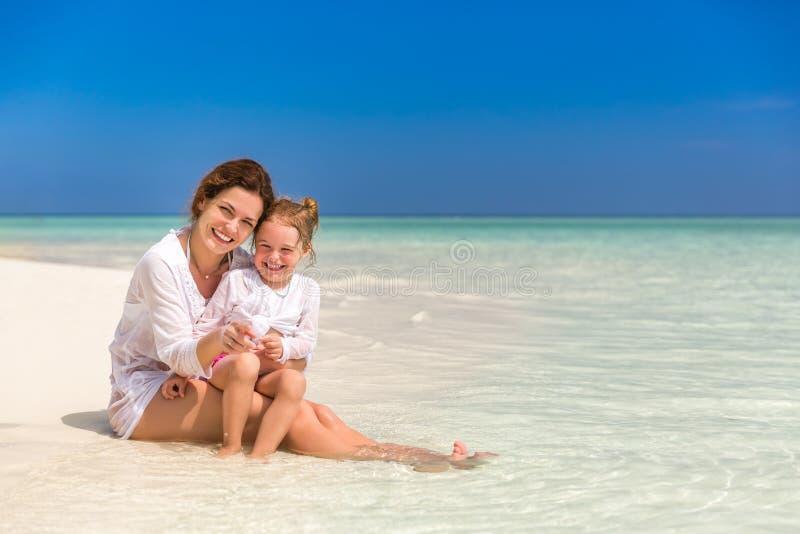 Moder och liten dotter på stranden royaltyfria bilder