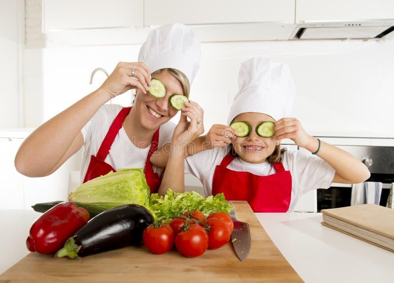 Moder och liten dotter som lagar mat tillsammans att spela med gurkaskivor på ögonen royaltyfri bild