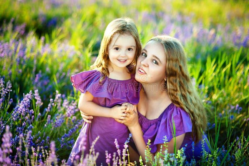 Moder och liten dotter som tillsammans spelar i en parkera modern kysser försiktigt hennes lilla dotter royaltyfri bild
