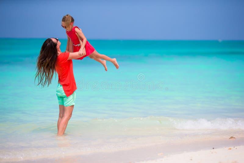 Moder och liten dotter som tycker om tid på den tropiska stranden arkivfoto