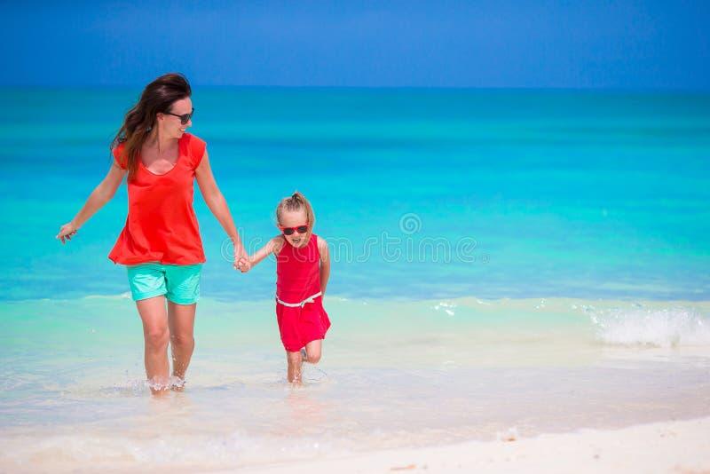 Moder och liten dotter som tycker om tid på den tropiska stranden arkivfoton