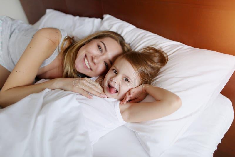Moder och liten dotterblick på kameran som ler på vit säng med solsken fotografering för bildbyråer