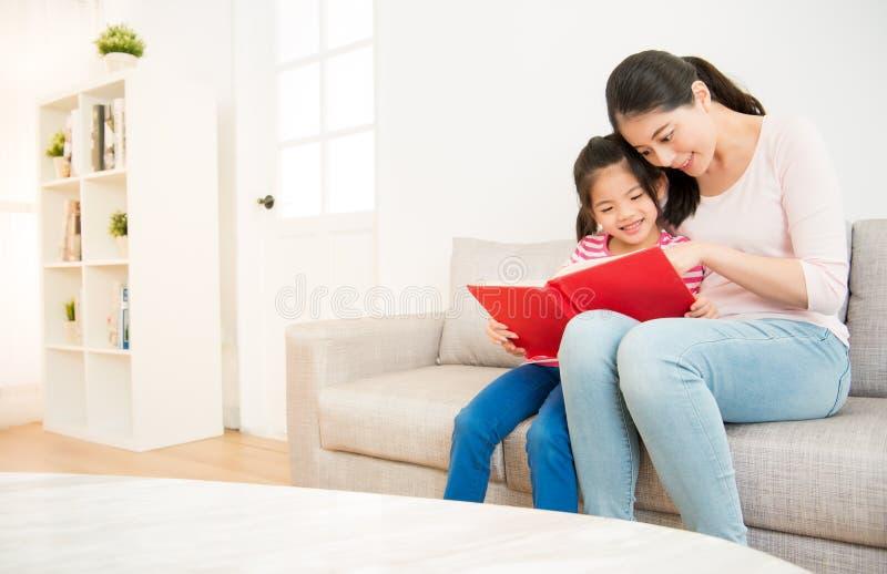Moder och liten flicka som läser en bok arkivbilder