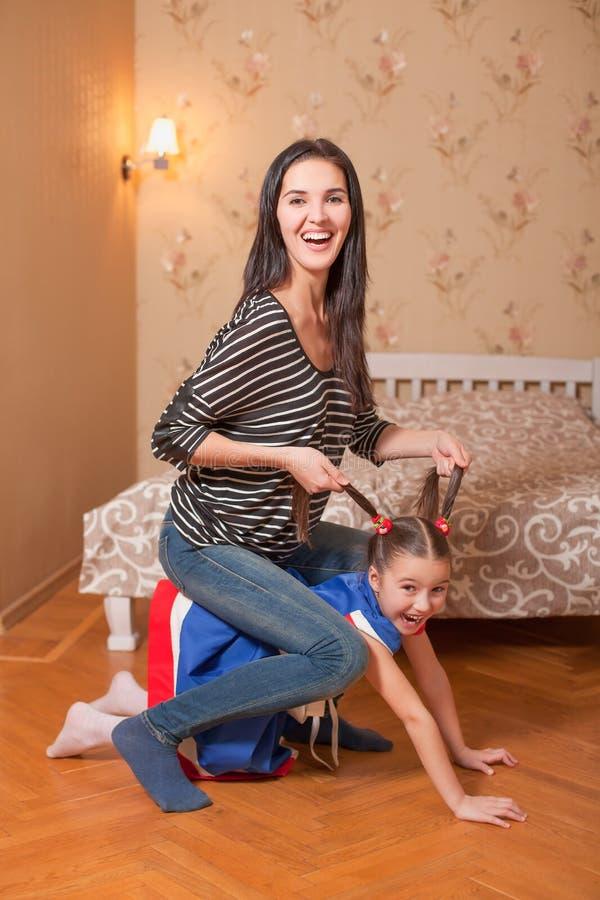 Moder och liten flicka som spelar en häst fotografering för bildbyråer