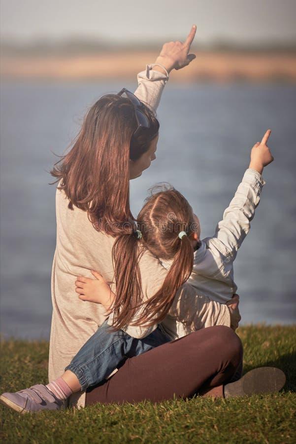 Moder och liten flicka som tycker om tid som pekar tillsammans med fingret till himlen fotografering för bildbyråer