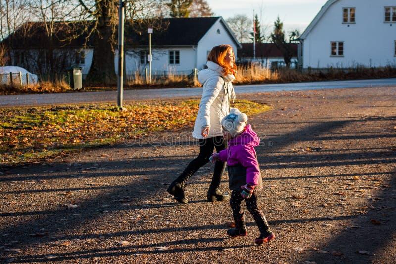 Moder och liten litet barnflicka som tillsammans går på vägen på solnedgången Modern och dottern går i parkera i evenien royaltyfria foton
