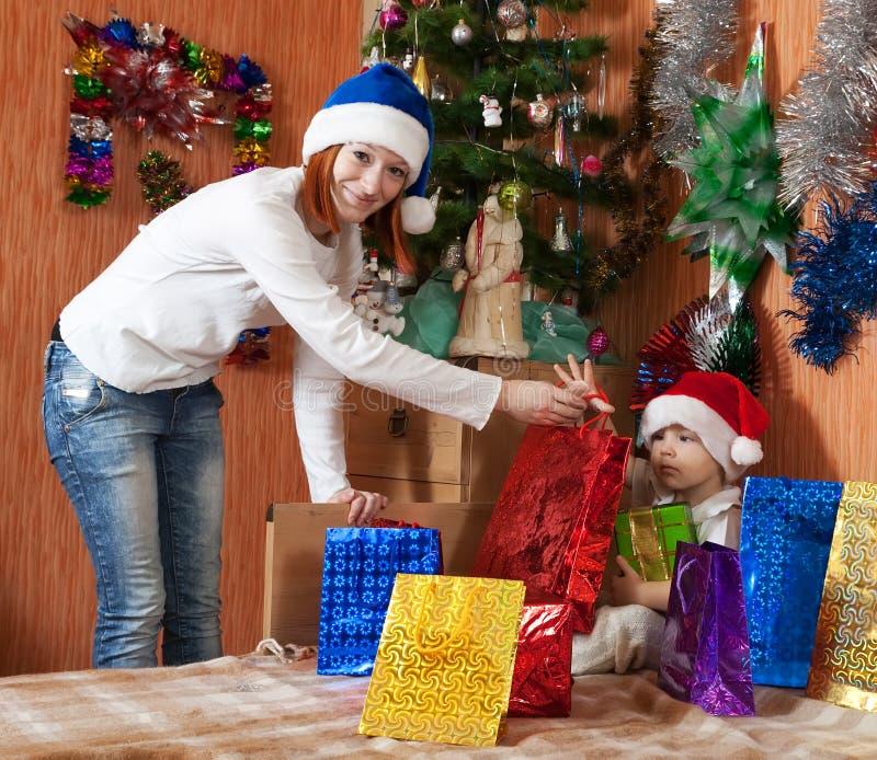 Moder och liten son med julgåvor arkivbilder