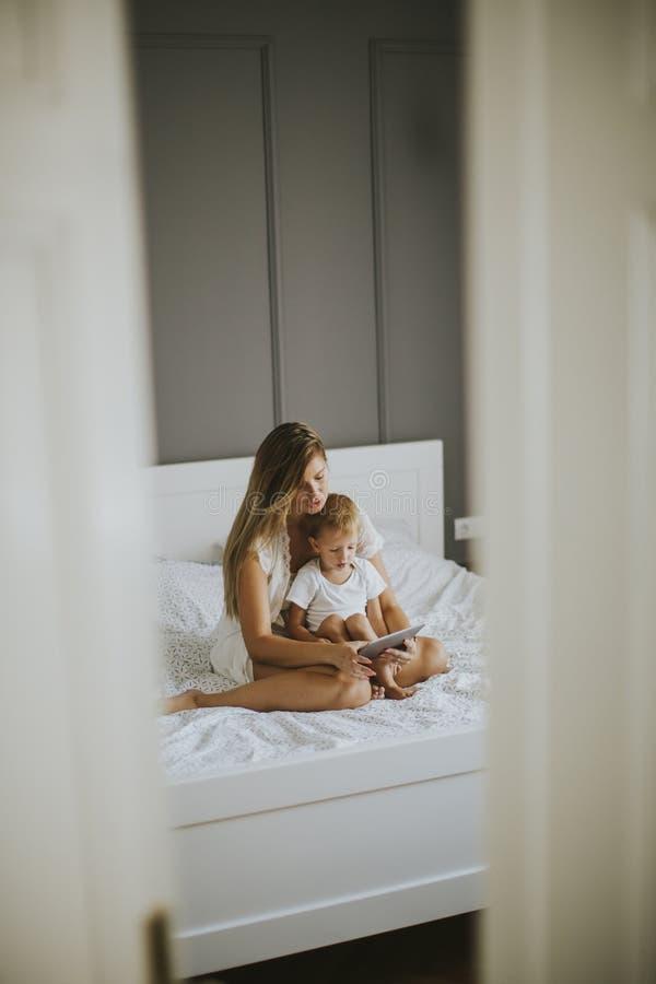 Moder och liten son med minnestavlan på säng royaltyfri fotografi