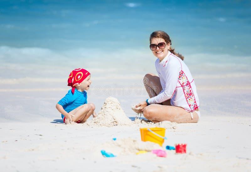 Moder och liten son som bygger en sandslott på stranden royaltyfria foton