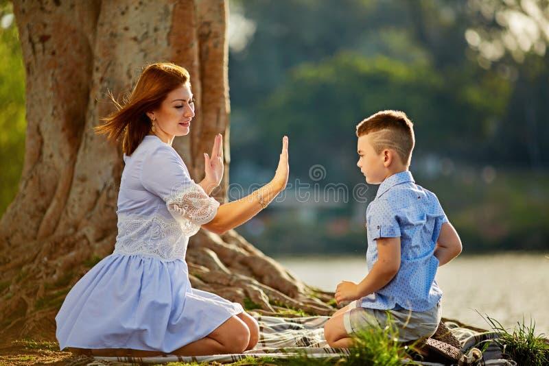 Moder och liten sonlek med sand Behandla som ett barn rymmer hennes händer till moderarmarna Utomhus- aktivitet för för aktivförä fotografering för bildbyråer