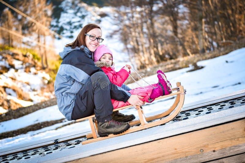 Moder och litet barn på en skidatransportör på pulkan royaltyfri fotografi
