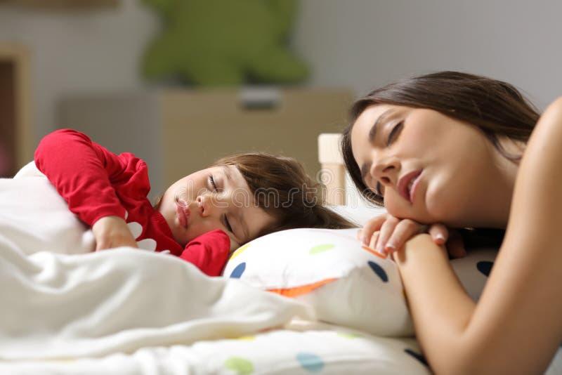 Moder och litet barn som sover i en säng arkivbilder