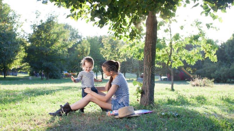 Moder och litet barn som spelar på trädgården royaltyfria bilder