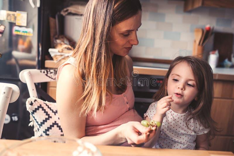 Moder- och litet barndotter som hemma äter druvor för frukost arkivbilder