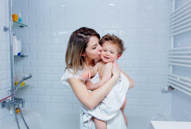 Moder- och litet barnpojke efter bad Moder som kysser en behandla som ett barn Barnet ser in till en kamera fotografering för bildbyråer