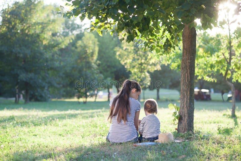Moder- och litet barnsammanträde under trädet arkivfoto