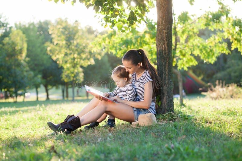 Moder- och litet barnsammanträde under trädet fotografering för bildbyråer