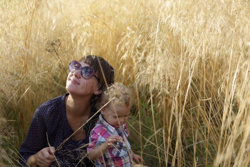 Moder och son i fält av gräs arkivbilder