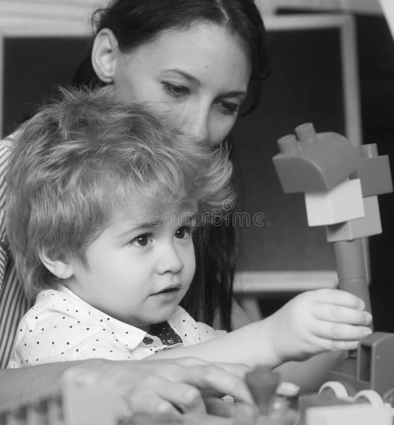 Moder och son i lekrum på mörk bakgrund royaltyfri fotografi