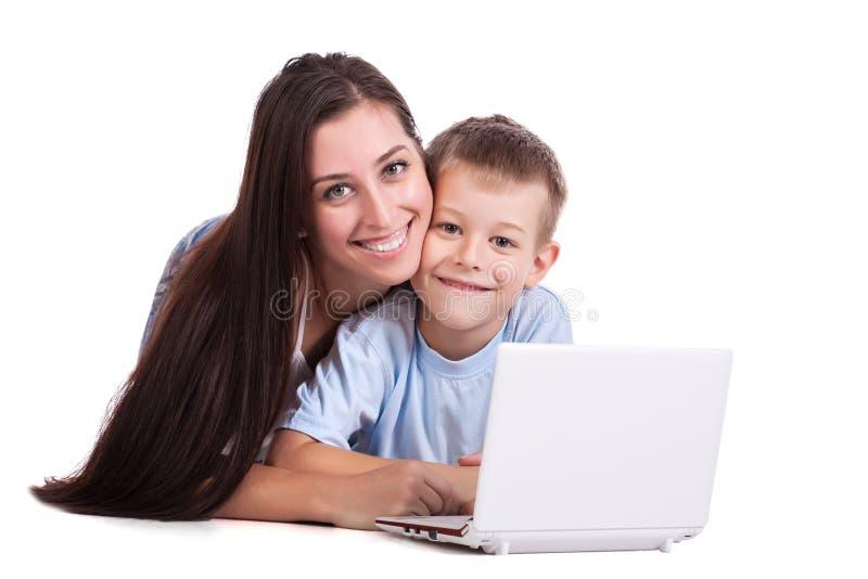 Moder och son med bärbar dator på white arkivfoton