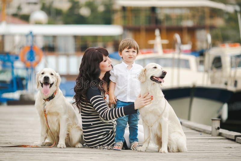 Moder och son med ett hundsammanträde på stranden royaltyfri fotografi