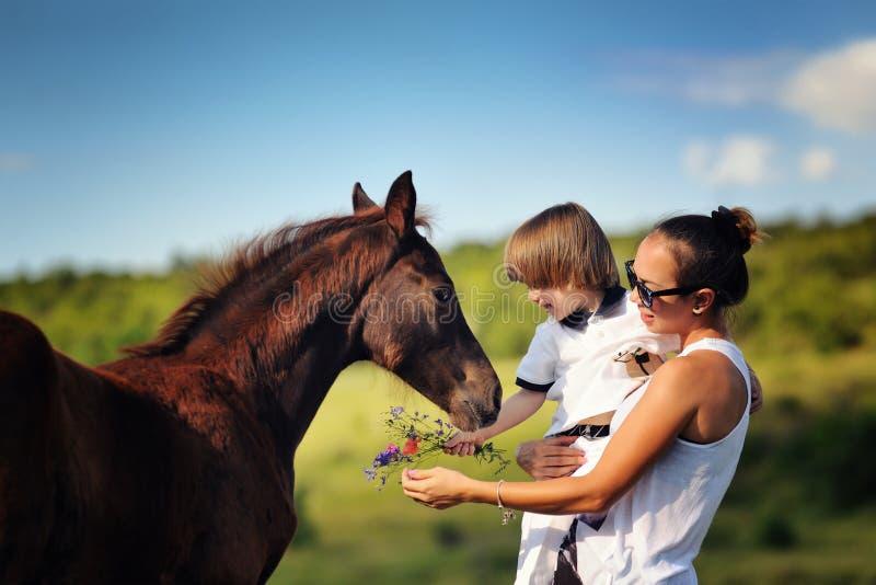 Moder och son med hästen arkivbild