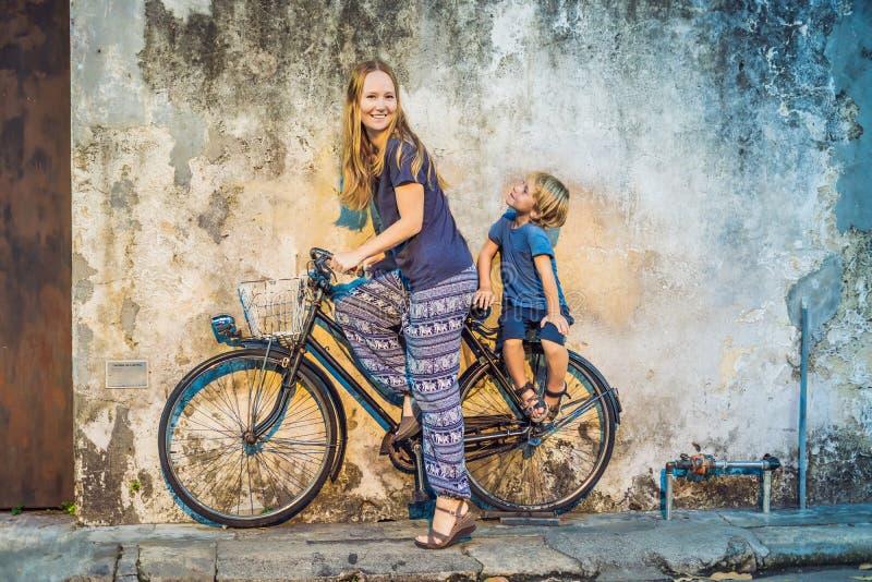 moder och son på en cykel Offentlig gatacykel i Georgetown, Penang, Malaysia arkivbild