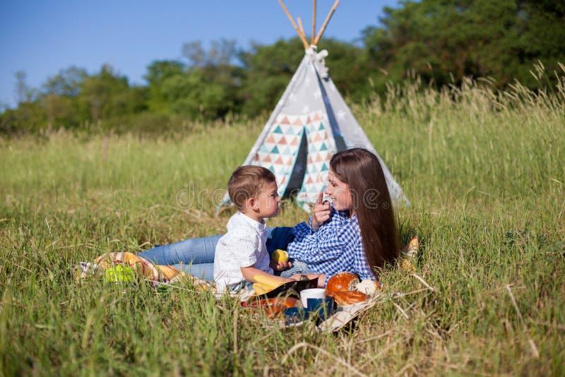 Moder och son på en picknick som äter utomhus ferie royaltyfri bild