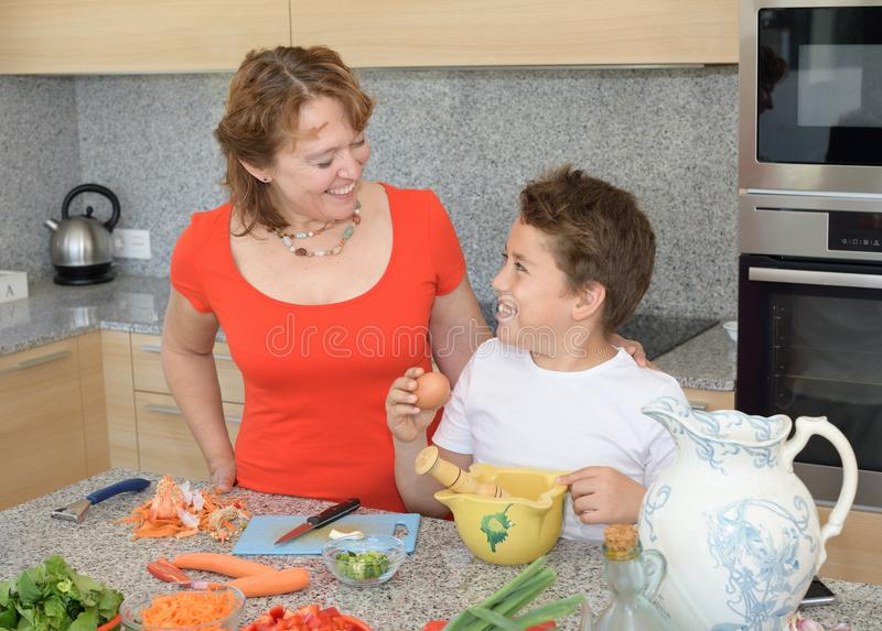 Moder och son som förbereder lunch genom att använda ägg och leende royaltyfri fotografi