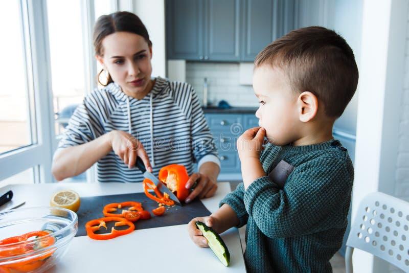 Moder och son som förbereder lunch i köket royaltyfri fotografi