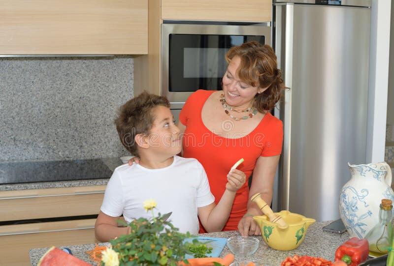 Moder och son som förbereder lunch och leende Barnet ger vitlök till hans moder arkivfoto