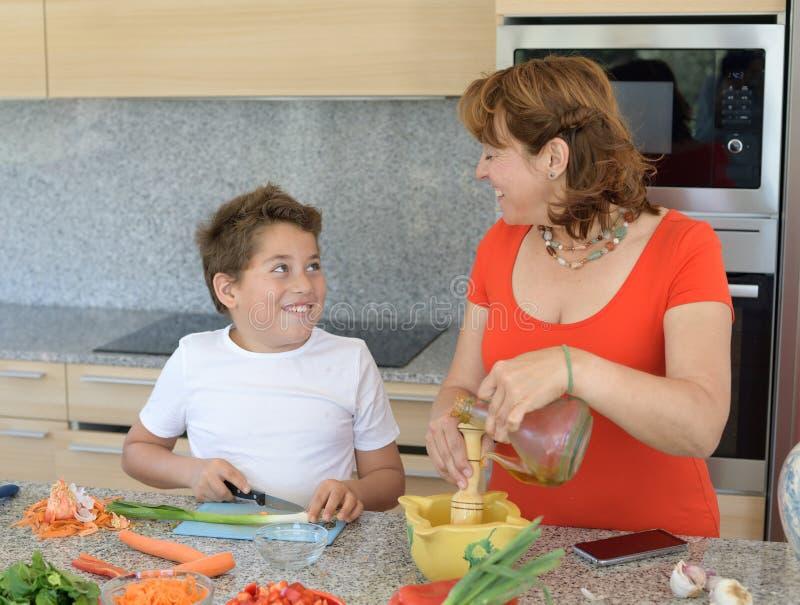 Moder och son som förbereder lunch och leende Sonen klipper vitlök royaltyfri bild