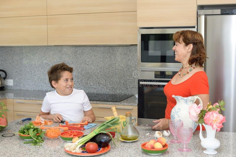 Moder och son som förbereder lunch och leenden Sonen klipper röd peppar royaltyfri foto
