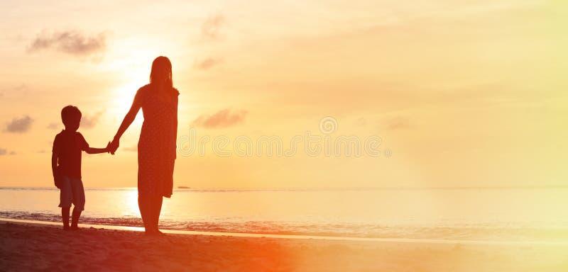 Moder och son som går på solnedgångstranden arkivfoto