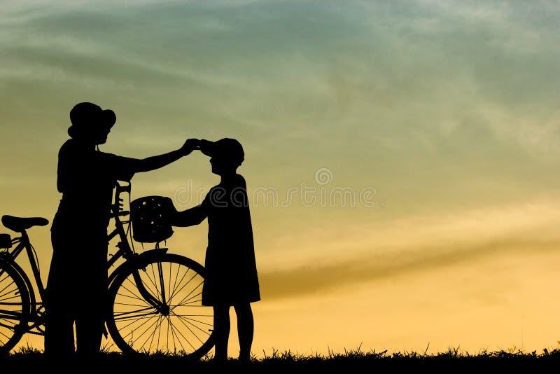 Moder och son som har den roliga ridningcykeln på solnedgången, kontur en unge på solnedgången, royaltyfri fotografi