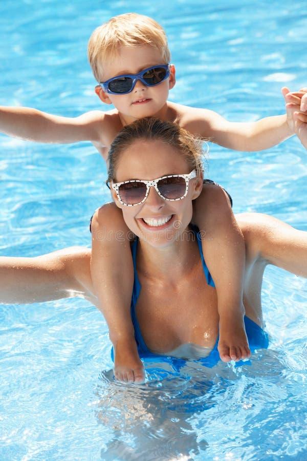 Moder och Son som har gyckel i simbassäng royaltyfri bild