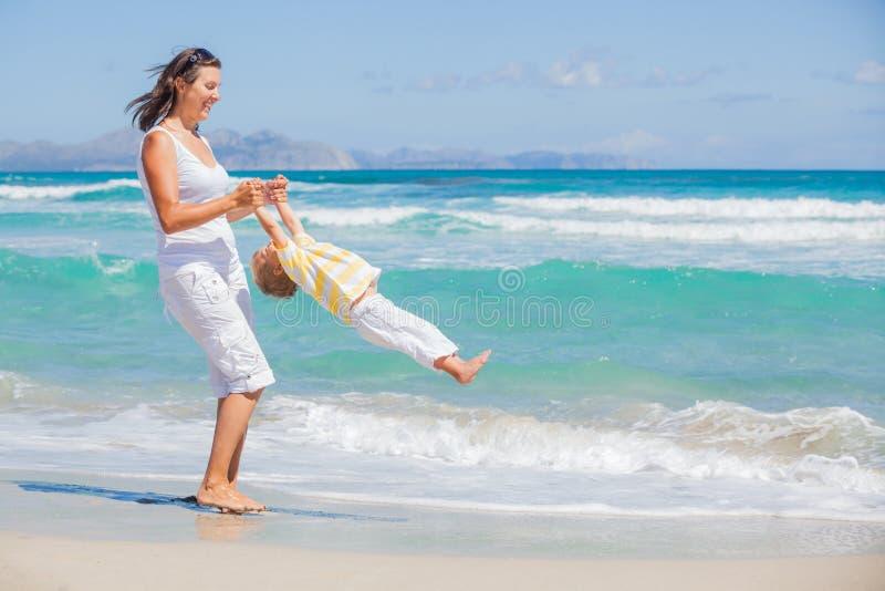 Moder och son som har gyckel på strand royaltyfri bild